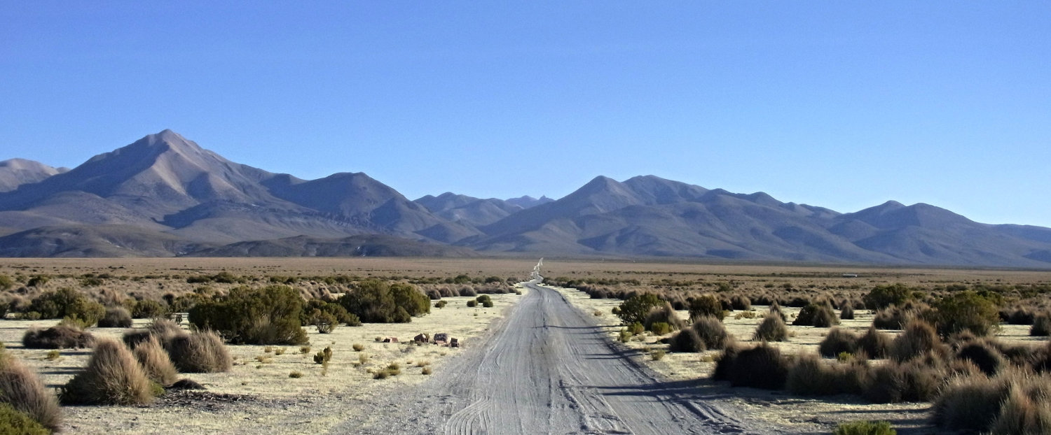 Bolivian alto plano - gravel road to vanishing point with mountains in the distance