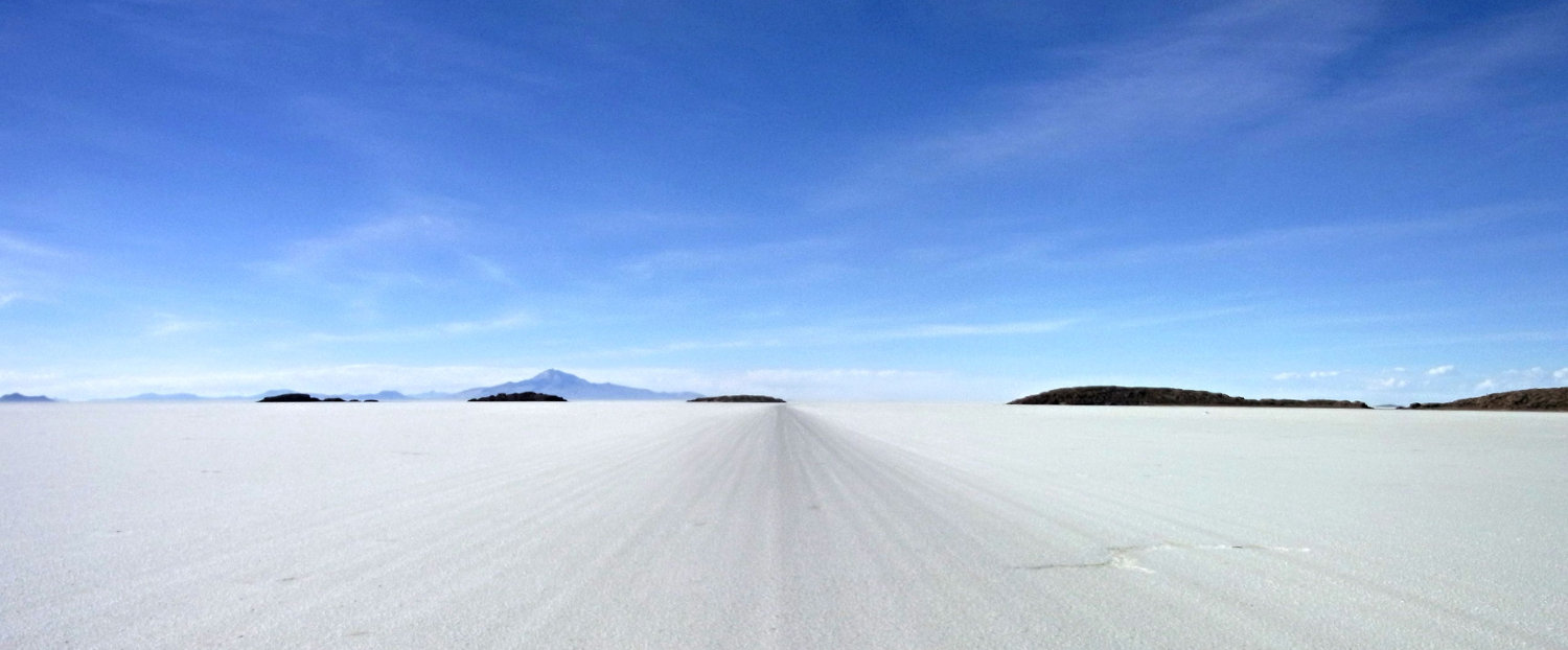 road going to vanishing point on the salar de uyuni with islands and mountains in the distance